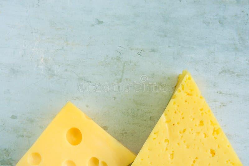 Klumpen und Keil des alpinen sahnigen appetitanregenden gelben Tilsiters und des Maasdam-Käses auf verkratztem Grey Metal Backgro stockfotos