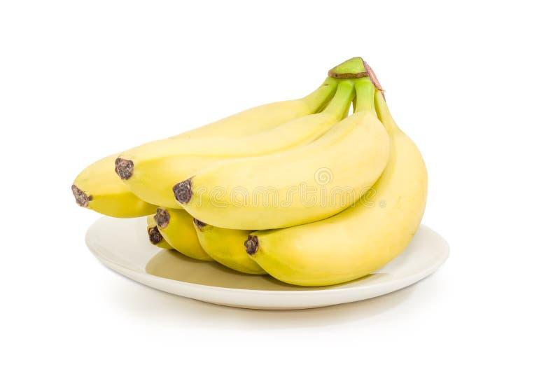 Klunga av bananer på en vit maträtt royaltyfri fotografi