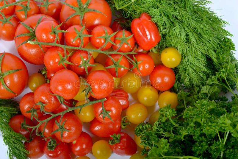 Klunga av små röda tomater med gräsplan royaltyfri bild