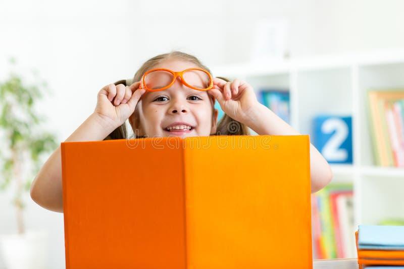 Klyftig barnflicka bakom av den öppna boken inomhus royaltyfria foton