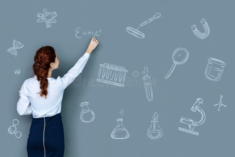 Klyftig lärare av kemi som känner sig som är glad, medan skriva formler royaltyfri fotografi