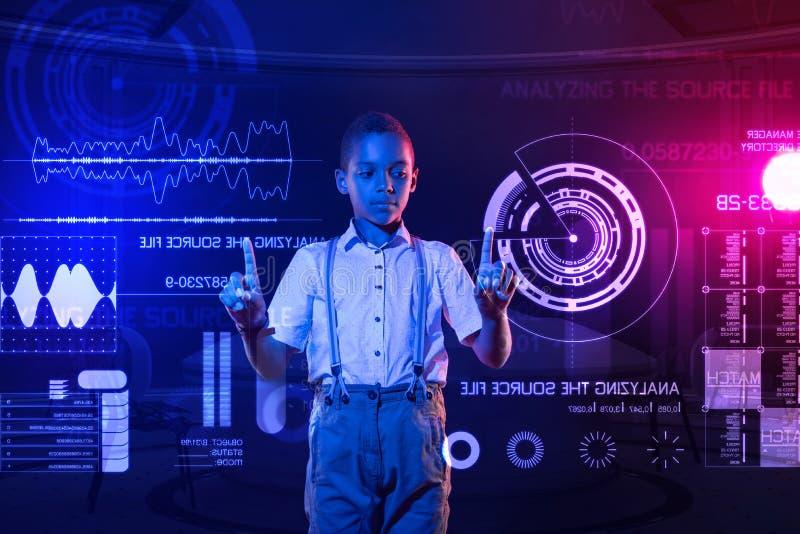 Klyftig pojke som jämför säkerhetssystem och trycker på skärmen arkivfoto