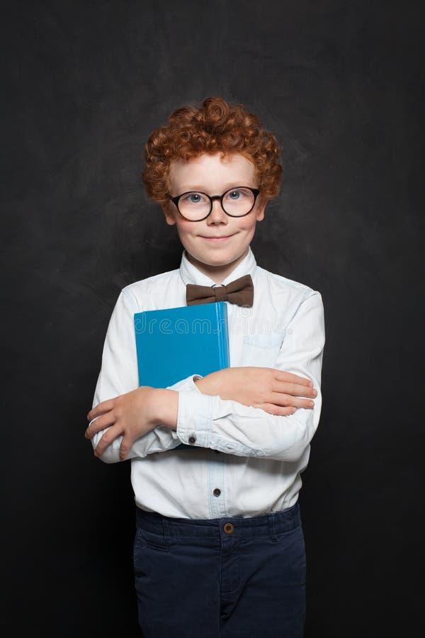 Klyftig unge med boken på svart tavlabakgrund Gullig rödhårig manbarnpojke på svart tavlaståenden royaltyfri foto