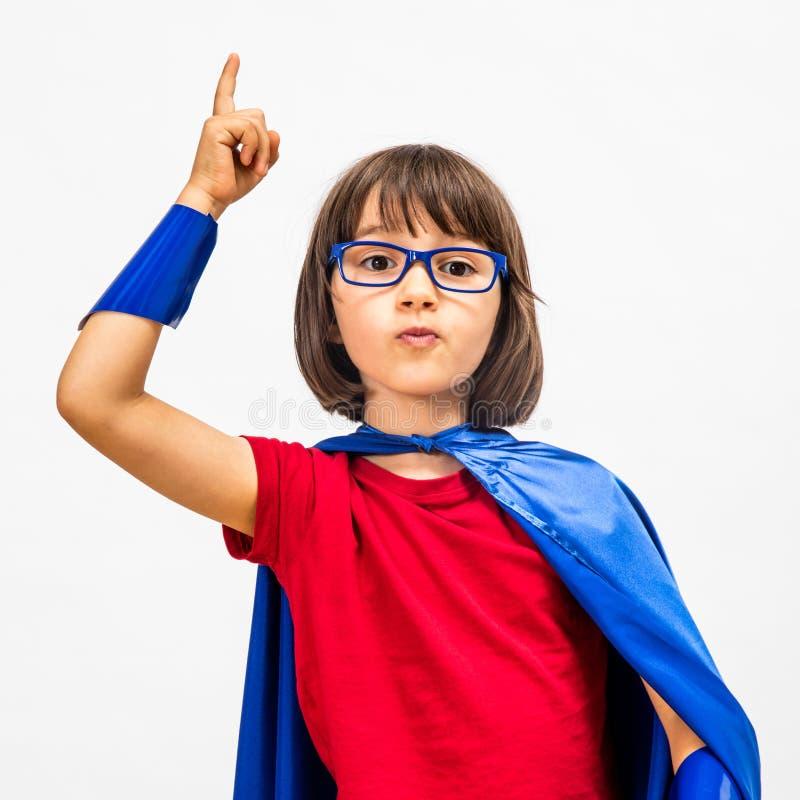 Klyftigt barn för toppen hjälte som lyfter hennes finger för överraskande idé arkivfoton