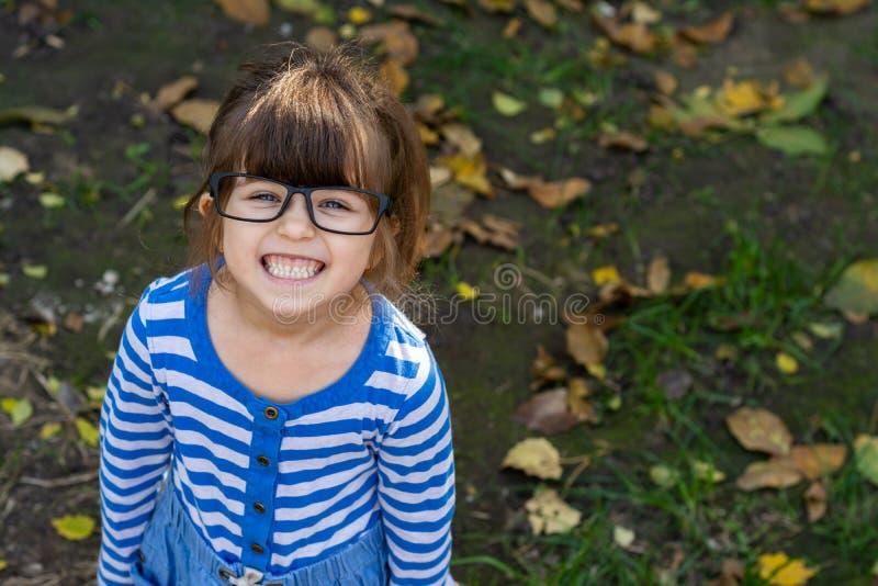 Klyftigt barn med glasögon som ler och ser kameran Ung elev som är klar för studie på skola arkivbild