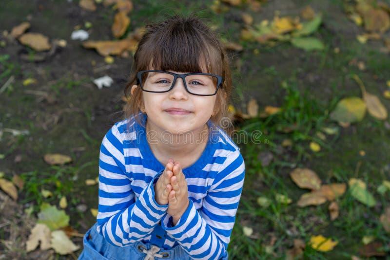 Klyftigt barn med glasögon som ler och ser kameran Ung elev som är klar för studie på skola Oj behaga! arkivbilder