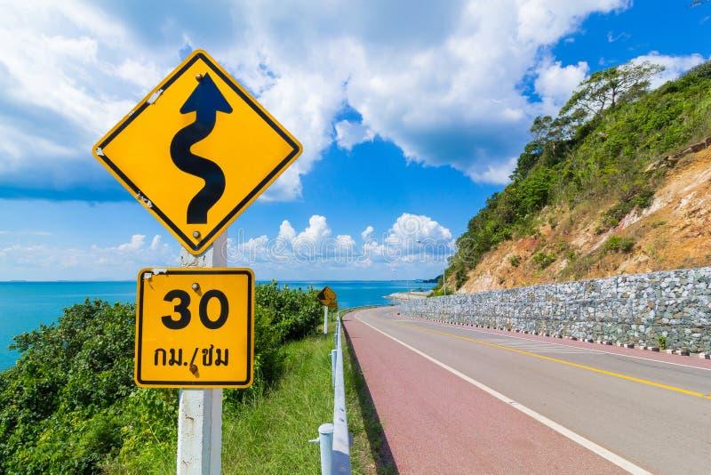 30 km/小时的限速标志和当心河曲标志 免版税库存图片