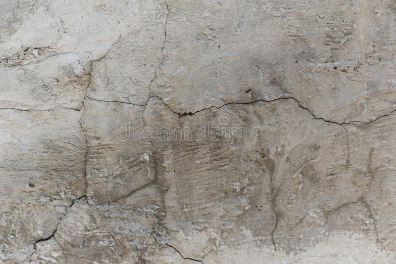 knäckt betongvägg som täckas med grå murbrukyttersida som bakgrund arkivbild