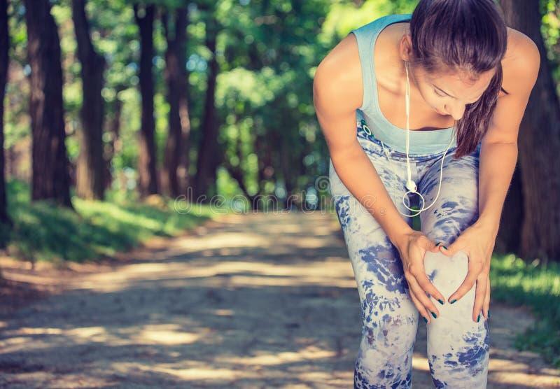 Knäet för löparen för den kvinnliga idrottsman nen smärtar det rörande in, konditionkvinnan som spring parkerar in royaltyfri fotografi