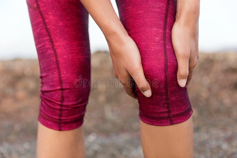 Knäet smärtar kvinnan för löparen för idrottsman nen för springbenskadan arkivbild