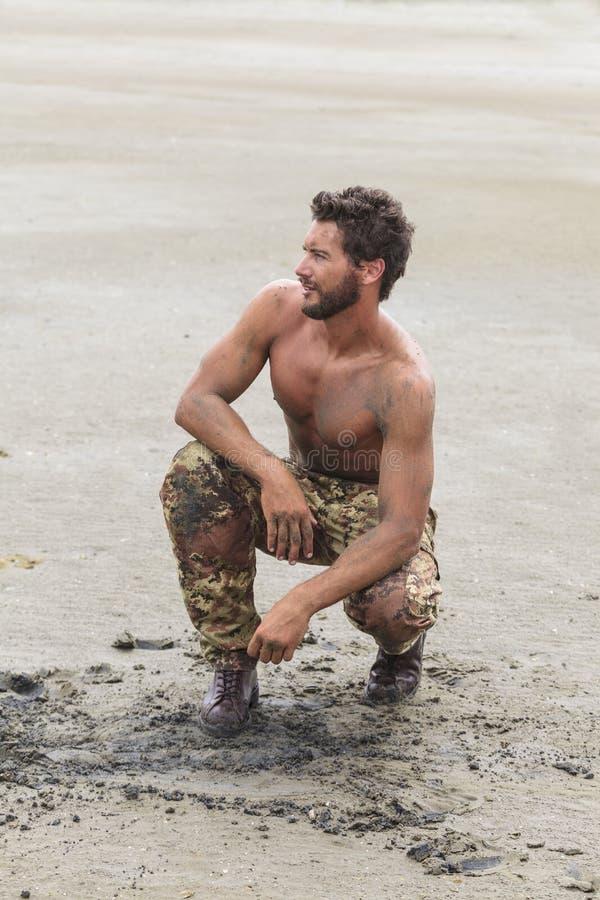 Knäfalla Shirtless soldat på strandsanden royaltyfri foto