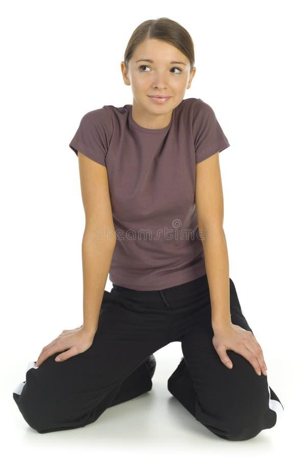 knäfalla träningsoverallkvinna royaltyfria bilder