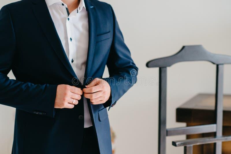 Knäppas ett omslag räcker tätt upp Den stilfulla mannen i dräkt fäster knappar och rätar ut hans omslag som förbereder sig att gå royaltyfri foto
