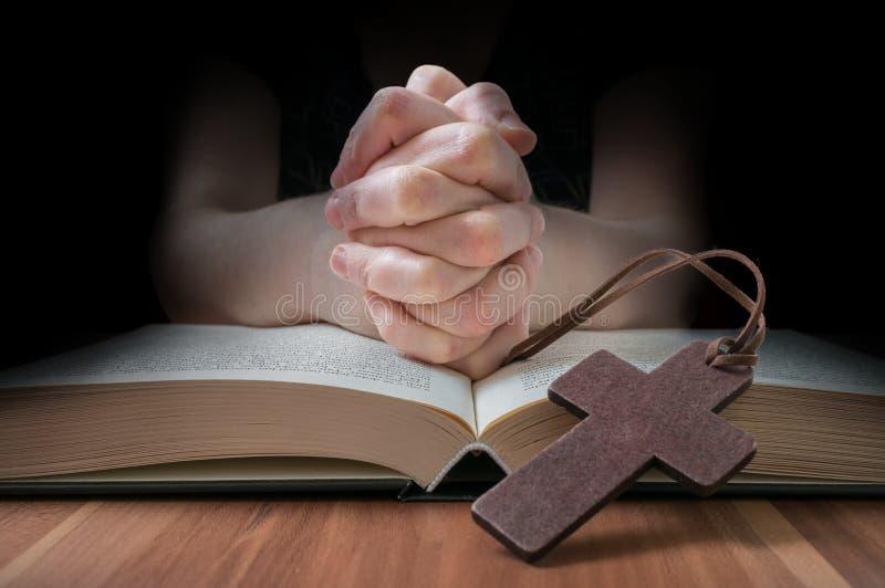 Knäppte fast händer av bönen Lågt nyckel- foto royaltyfria bilder