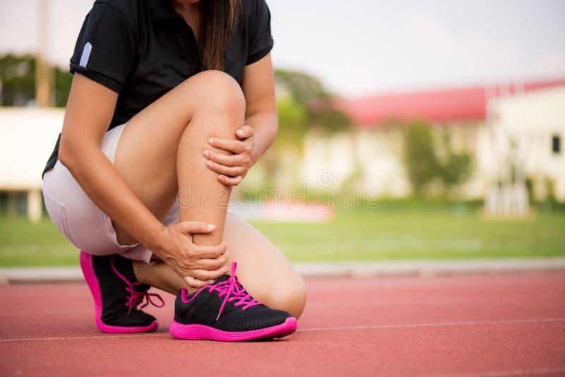 Knöchel verstaucht Junge Frau, die unter einer Knöchelverletzung leidet stockfoto