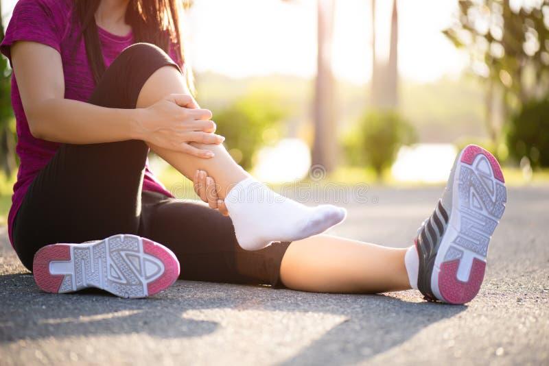 Kn?chel verstaucht Junge Frau, die unter einer Kn?chelverletzung beim Trainieren und Laufen leidet Gesundheitswesen- und Sportkon stockbild