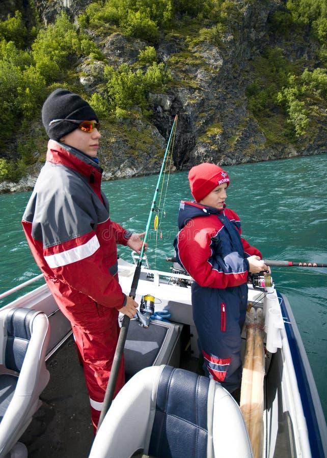 Knaben, die vom Boot fischen stockbild