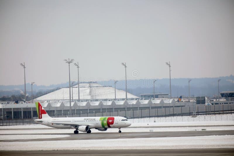 KNACKA LÄTT PÅ den Air Portugal nivån på landningsbana i den Munich flygplatsen, Tyskland, vintertid med snö royaltyfri fotografi