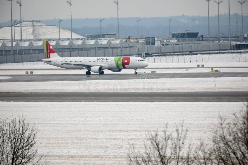 KNACKA LÄTT PÅ den Air Portugal nivån på landningsbana i den Munich flygplatsen, Tyskland, vintertid med snö royaltyfria foton