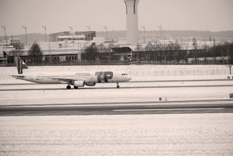 KNACKA LÄTT PÅ den Air Portugal nivån på landningsbana i den Munich flygplatsen, Tyskland, vintertid med snö arkivbilder