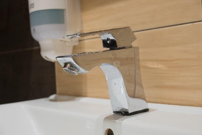 Knacka lätt på på vasken i den samma ställevätsketvålen, fyrkantigt klapp arkivfoton