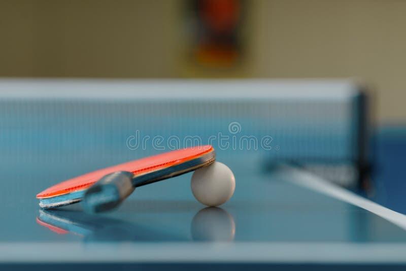 Knacka pongracket och klumpa ihop sig på den modiga tabellen, closeup arkivbilder