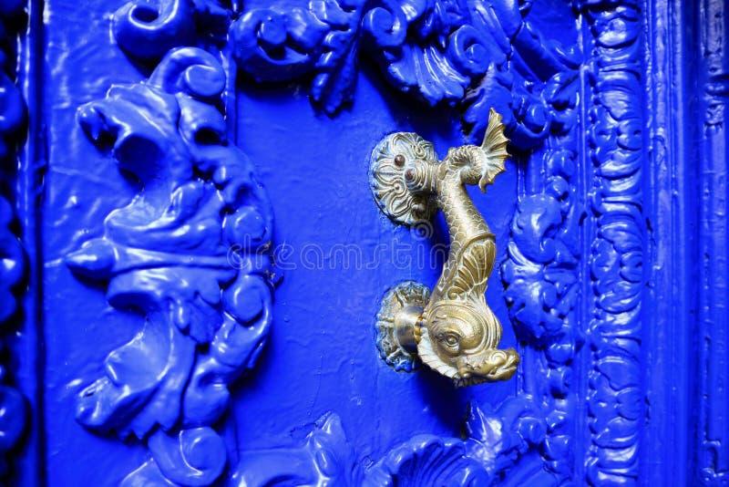 Knackaren för dörren för tappningstil sned delfin formade mässingspå livliga blått den wood dörren, Cuzco, Peru royaltyfria bilder