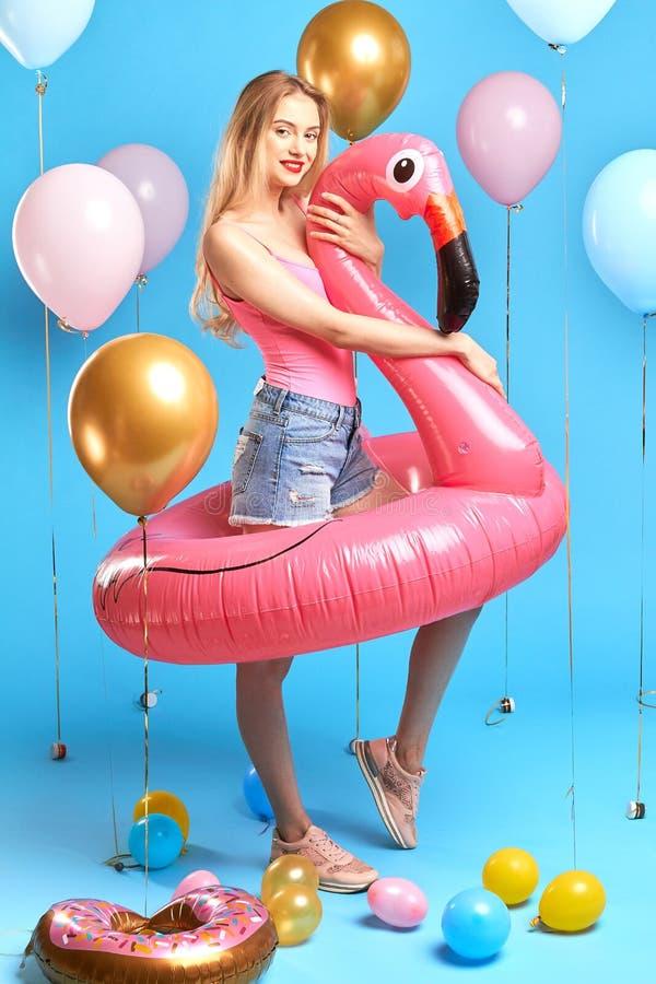 Knap blond meisje in roze bovenkant, denimjeans, trainers royalty-vrije stock fotografie