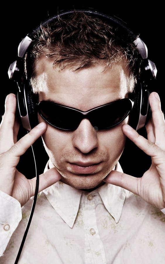 Knap DJ in zonnebril met hoofdtelefoons stock afbeelding