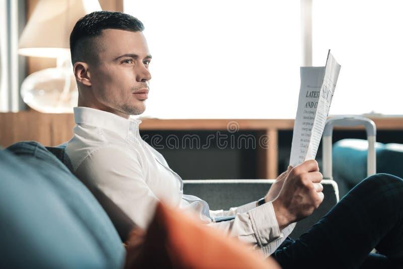Knap donkerharige die de witte krant van de overhemdsholding dragen stock fotografie
