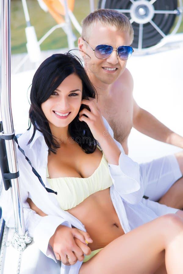 Knap en rijke man en een mooie en sexy vrouw in een zwempak stock fotografie