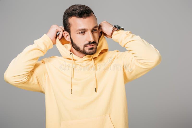knap gebaard mannelijk model die op gele hoodie zetten royalty-vrije stock afbeelding