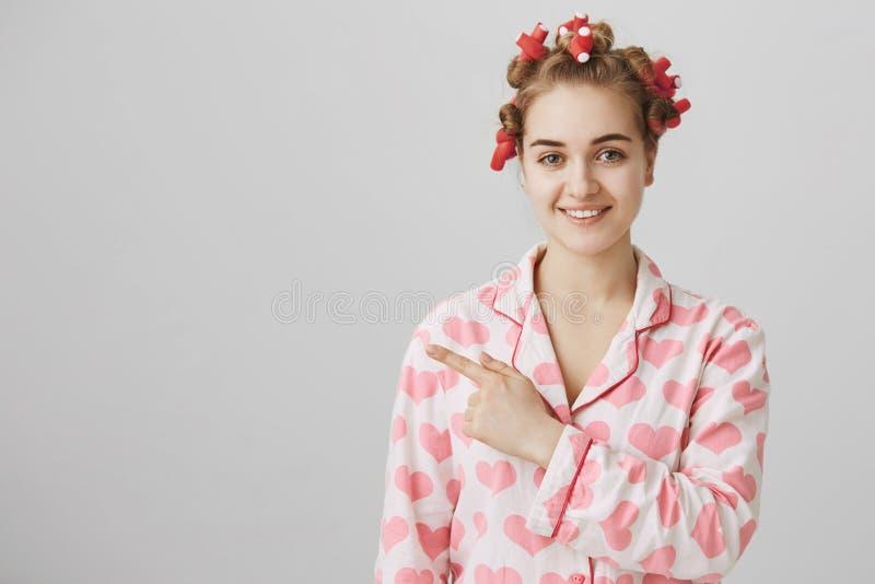 Knap grappig Kaukasisch wijfje in charmingly en haar-krulspelden die links of, zich bevindt over grijs glimlachen erachter richte royalty-vrije stock foto's