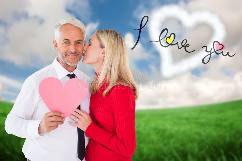 Knap het document van de mensenholding hart die een kus van vrouw krijgen stock fotografie