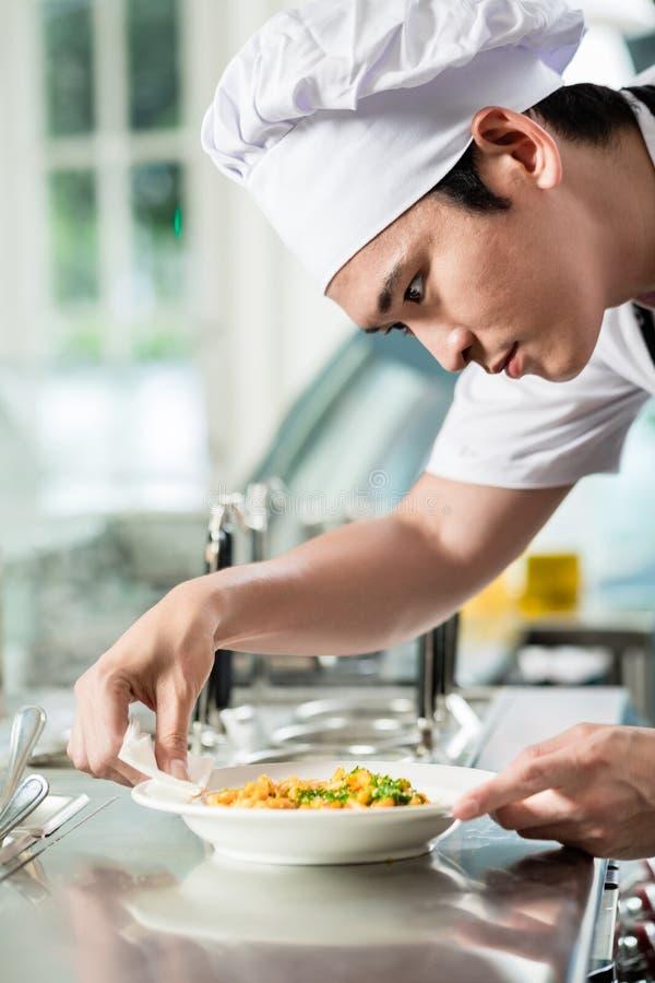 Knap jong Aziatisch chef-kokplateren op voedsel royalty-vrije stock afbeelding