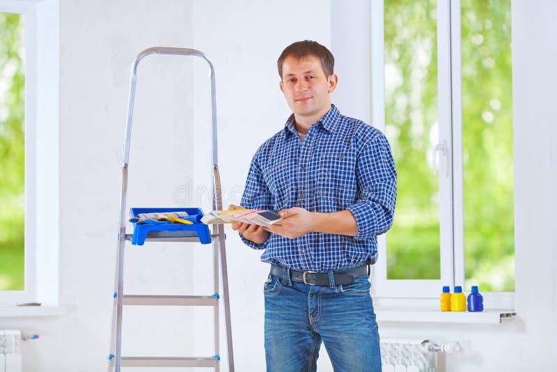 Knap jong de kleurenpalet van de huiseigenaarholding en het bekijken ca stock afbeelding