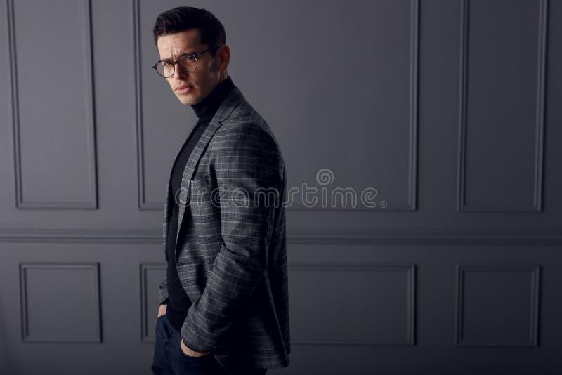 Knap jong donkerbruin model, die in grijs jasje dragen, die met houding, op grijze achtergrond kijken De ruimte van het exemplaar royalty-vrije stock afbeelding