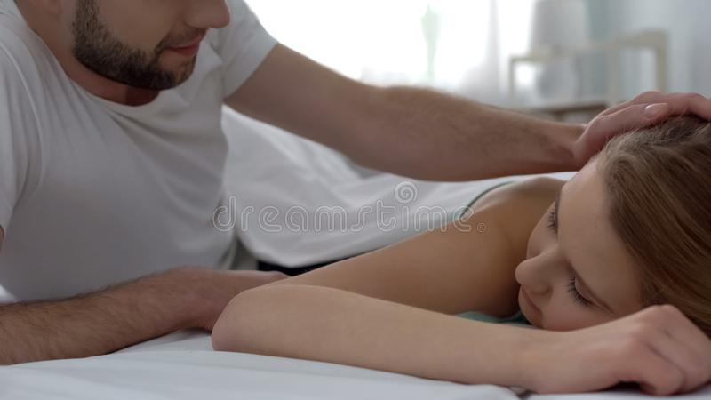 Knap jong echtgenoot het strijken vrouwenhaar met tederheid in ochtend, wittebroodsweken stock foto's