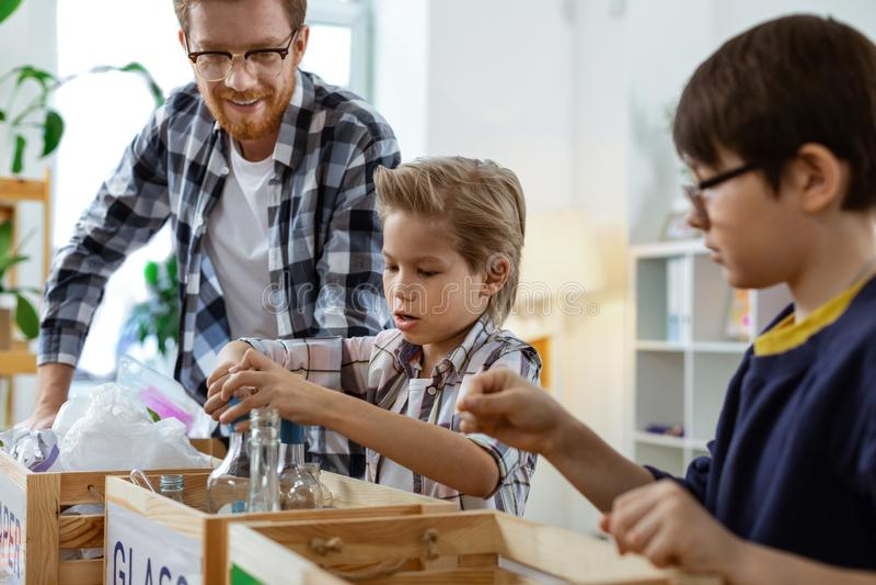 Knap jong kind die resoluut huisvuil en afval bestrijden stock afbeelding