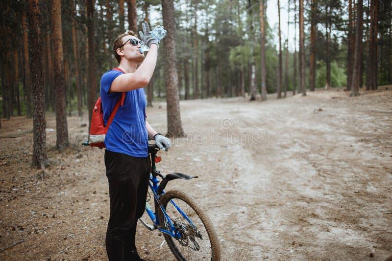 Knap jong mensen amateurl cyclistdrinking water van de fles, die van fiets in pijnboom bosrecreatie genieten van royalty-vrije stock foto's