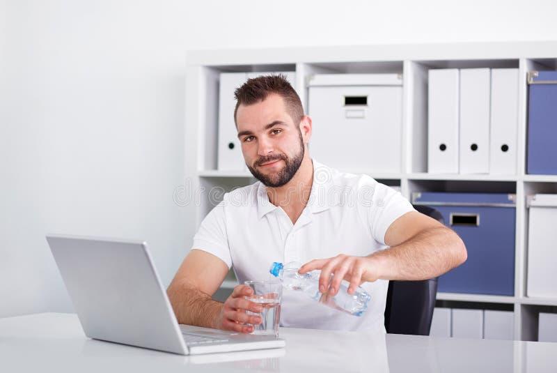 Knap jonge mensen gietend water in een glas stock fotografie