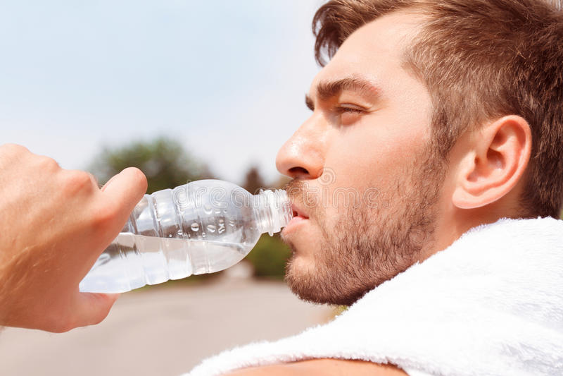 Knap kerel drinkwater stock foto's
