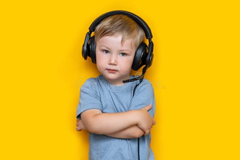 Knap leuk blonde weinig jongen drie jaar oud in gokken zwarte hoofdtelefoons bekijk camera, grijze ogen en grijze t-shirt op geel stock afbeeldingen