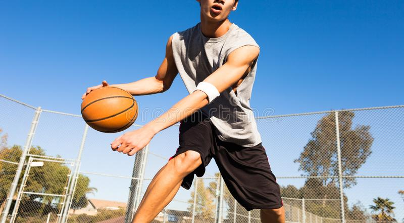 Knap mannelijk speelbasketbal openlucht stock foto's