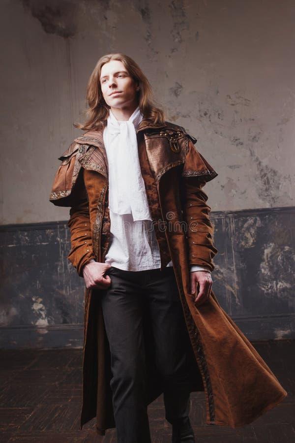 Knap mannetje in bruine mantel, Stoom punkstijl Retro mensenportret over grungeachtergrond royalty-vrije stock foto