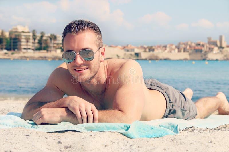 Knap mannetje die op het zand liggen royalty-vrije stock afbeelding