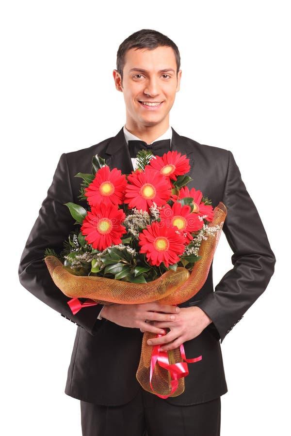 Knap mannetje met een boeket van bloemen stock fotografie
