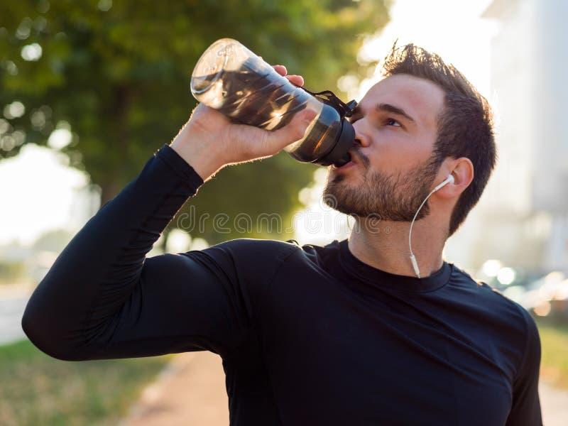 Knap mensen drinkwater op een zonnige dag royalty-vrije stock foto's