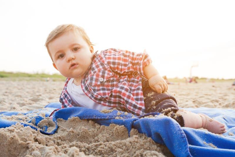 Knap nieuwsgierig kind die op zand op het strand liggen royalty-vrije stock foto