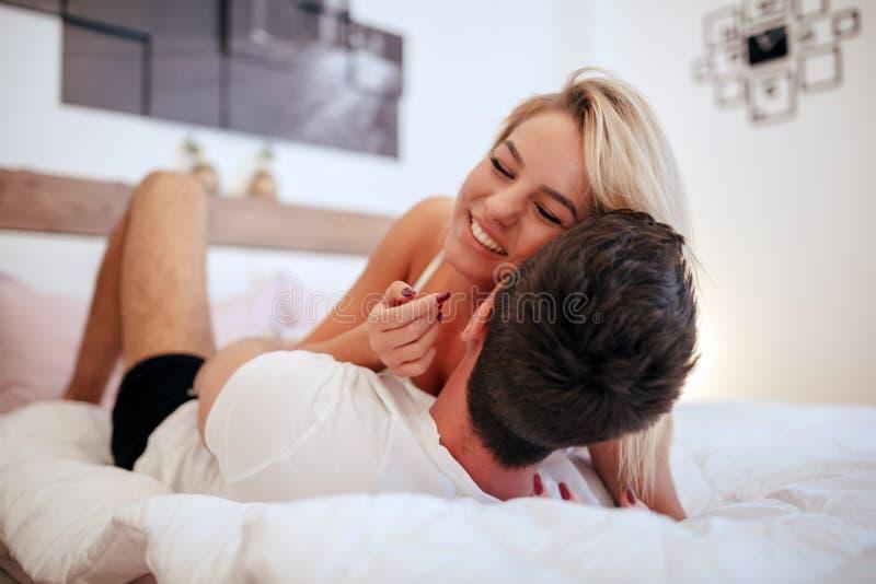Knap paar in bed die sensueel zijn stock foto's